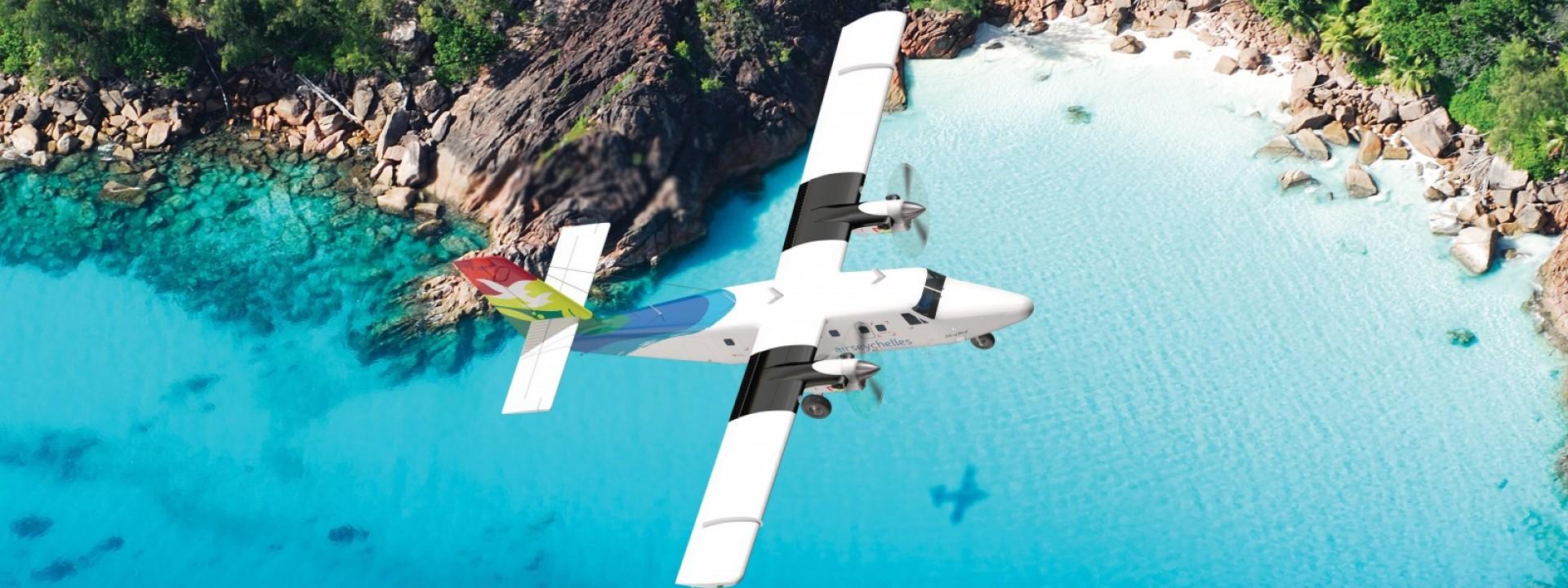 Air Seychelles Domestic Twin Otter volando sopra la spiaggia dell'isola