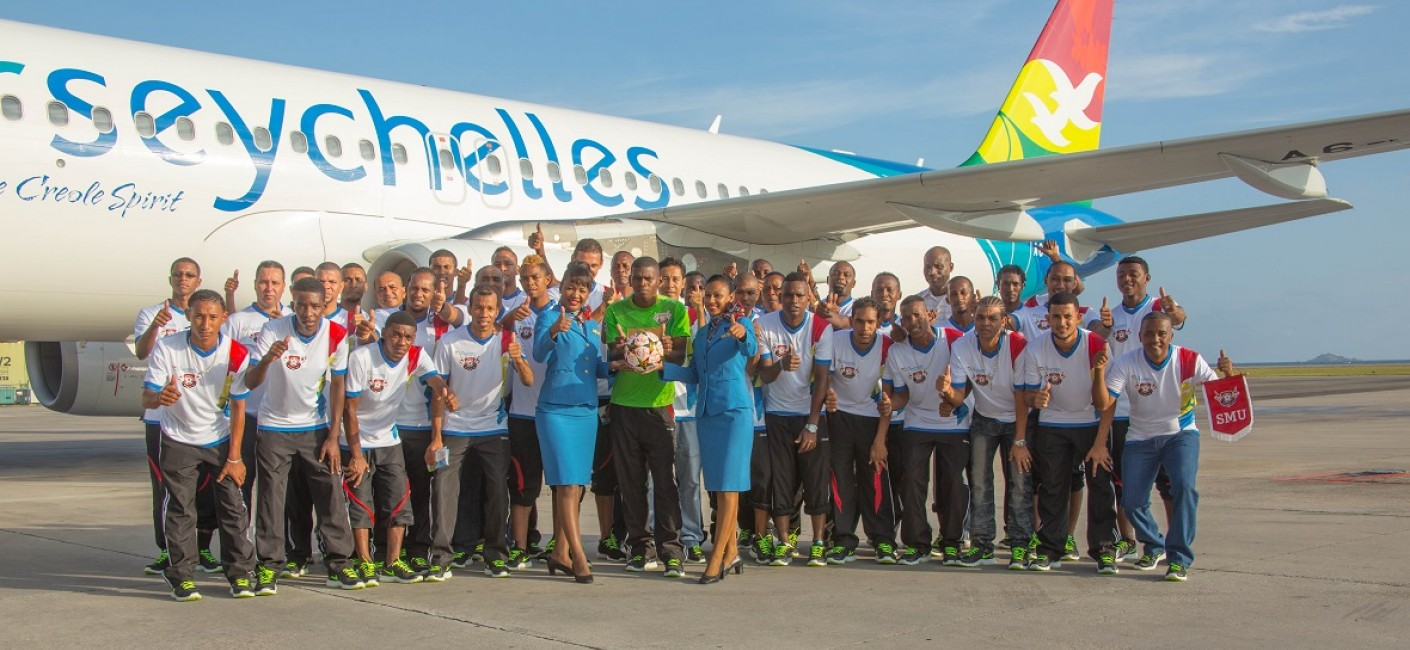 St Michel United players pose with Air Seychelles cabin crew before their early morning flight to South Africa