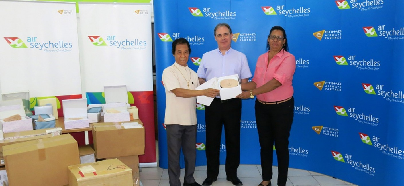 Bishop Chang Him, Chairman of the Cancer Concern Association, Roy Kinnear, Chief Executive Officer of Air Seychelles, and Elizabeth Julienne, mother of Dr Sophia Harryba, hold one of 177 prostheses flown to Seychelles by Air Seychelles and Etihad Airways