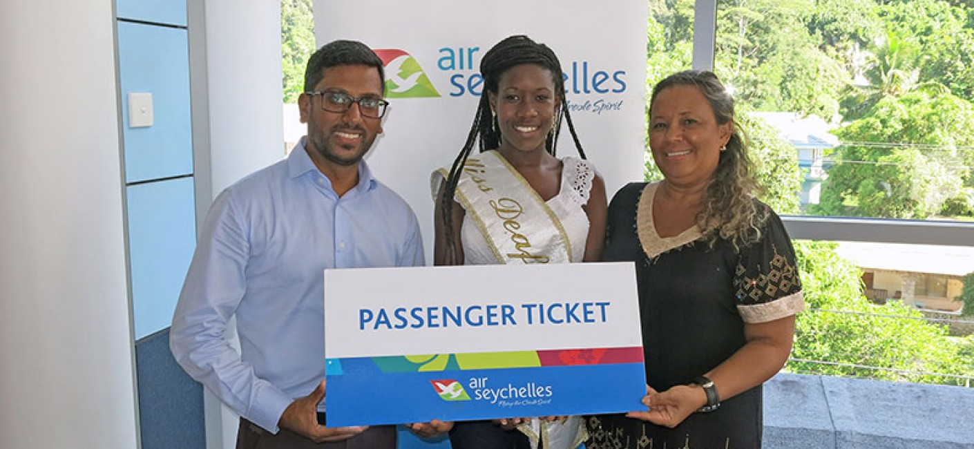 Manoj Papa, Chief Executive Officer of Air Seychelles, presents Melita Gilbert and Anita Gardner with tickets to South Africa before their departure.