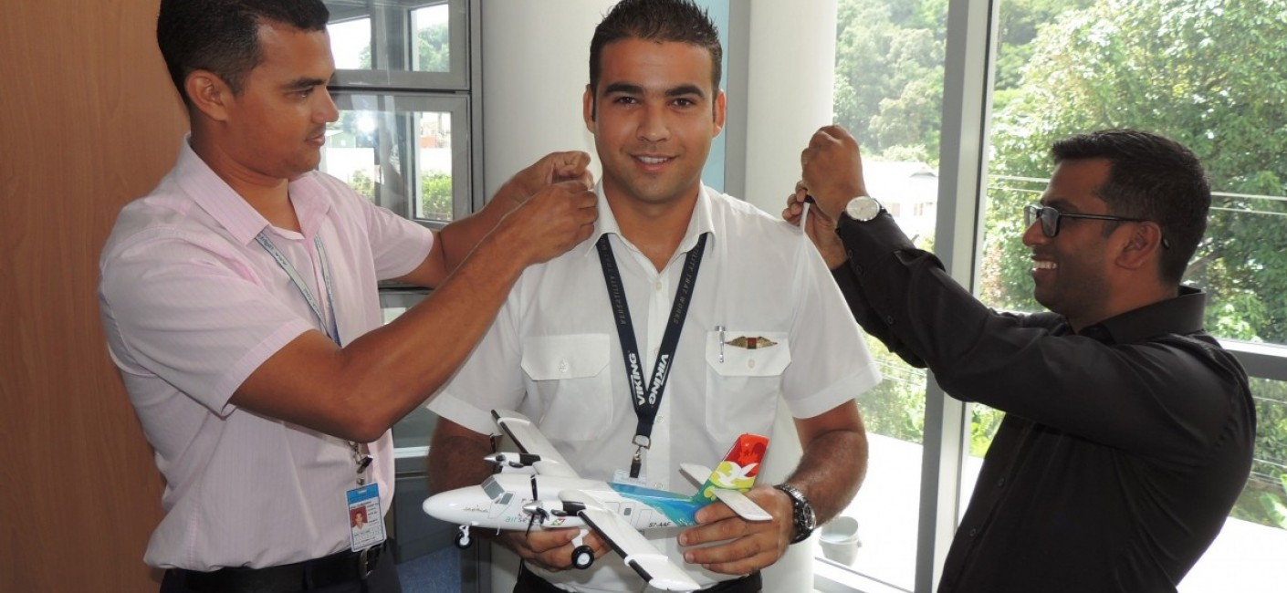 Captain Allen Dubignon, Chief Pilot Domestic (left), and Manoj Papa, Air Seychelles' Chief Executive Officer (right), fasten Captain Mein's commander's bars