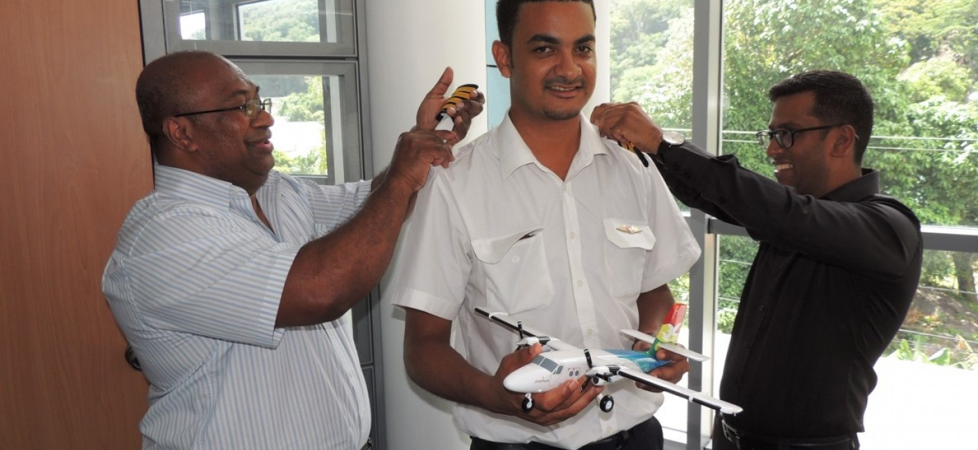 Captain Granger Narara, Head of Flight Operations (left), and Manoj Papa, Air Seychelles' Chief Executive Officer (right), congratulate Captain Romain on his promotion