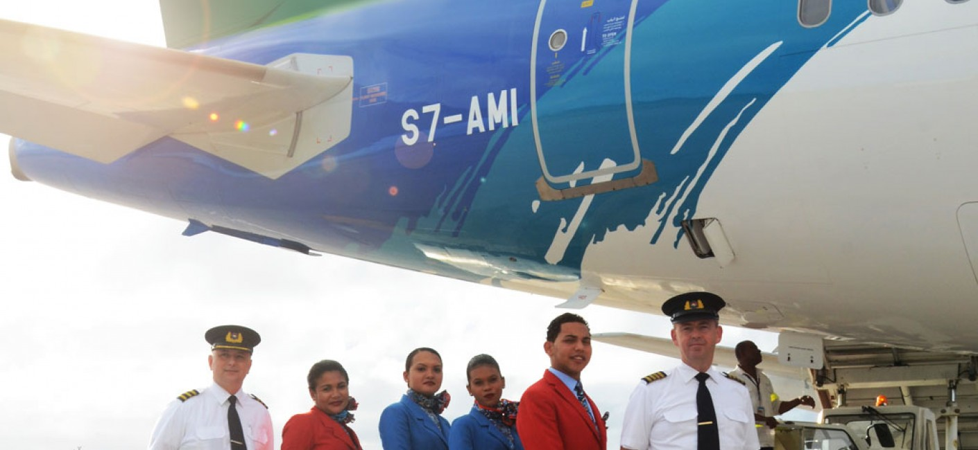 Air Seychelles pilots and cabin crew stand proudly in front of the airline's first Airbus aircraft to be registered in Seychelles, an Airbus A320 with registration number S7-AMI