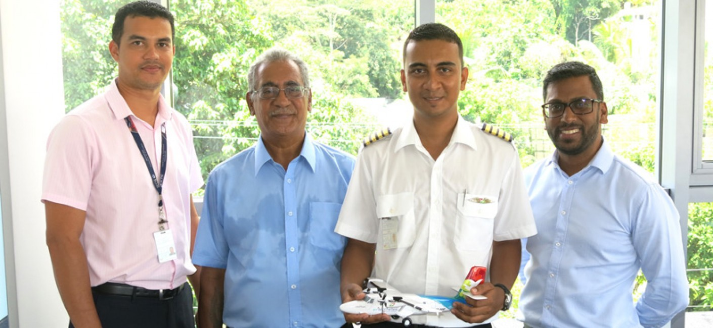 Allen Dubignon (first left), Chief Pilot Domestic, Purdy Quatre (second left), Administrator Ground Services Equipment and father of Captain Aubrey Quatre and Manoj Papa (right), Air Seychelles' Chief Executive Officer, congratulate the young pilot on his achievement.