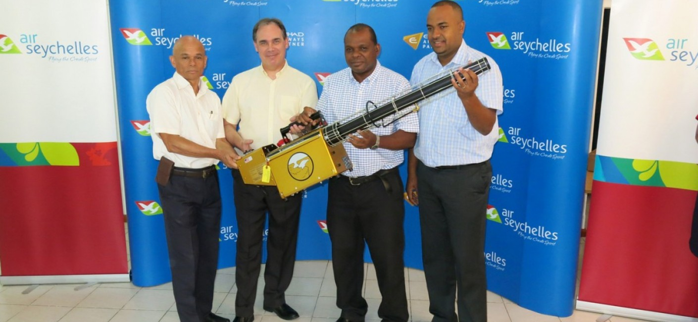 Paul Labaleine, Director General of DRDM, Roy Kinnear, Chief Executive Officer of Air Seychelles, Didier Dogley, Minister of Environment, Energy and Climate Change, and Wallace Cosgrow, Minister of Fisheries and Agriculture, hold a state-of-the-art insect fogger transported by Air Seychelles from South Africa.