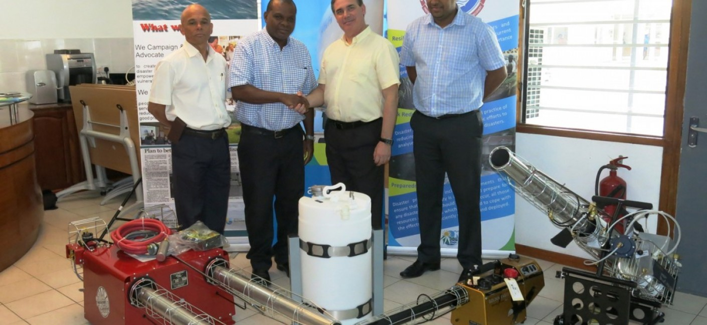 Paul Labaleine, Director General of DRDM, Didier Dogley, Minister of Environment, Energy and Climate Changem Roy Kinnear, Chief Executive Officer of Air Seychelles and Wallace Cosgrow, Minister of Fisheries and Agriculture, stand next to specialised fogging equipment transported by Air Seychelles.
