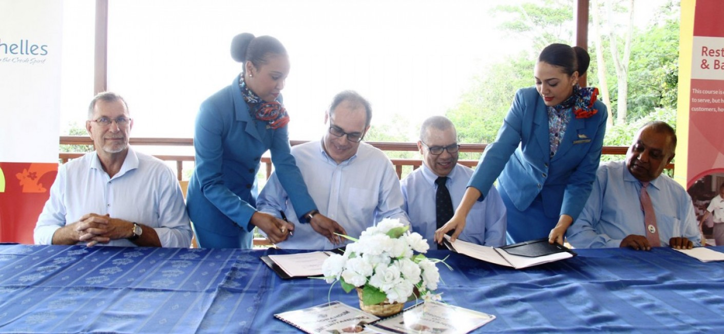(Centre) Roy Kinnear, Chief Executive Officer of Air Seychelles, and Flavien Joubert, Principal of the Seychelles Tourism Academy, sign an MoU covering areas of cooperation for employment and on-the-job training for students at the academy