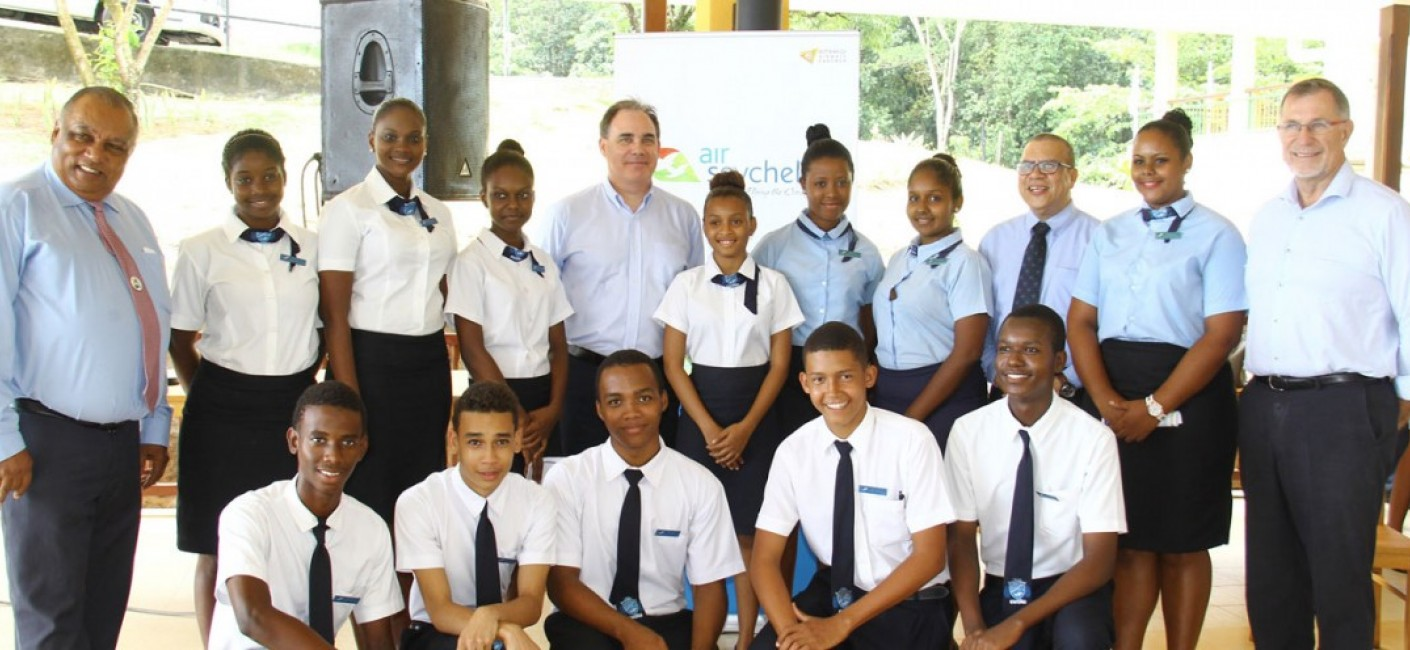 John Stravens, Chairperson of STA (first left), Roy Kinnear, Chief Executive Officer of Air Seychelles (fifth from left), Flavien Joubert, Principal of STA (third from right) and Peter Carrie-Wilson, General Manager Human Resources at Air Seychelles (first from right), stand next to current students at the STA